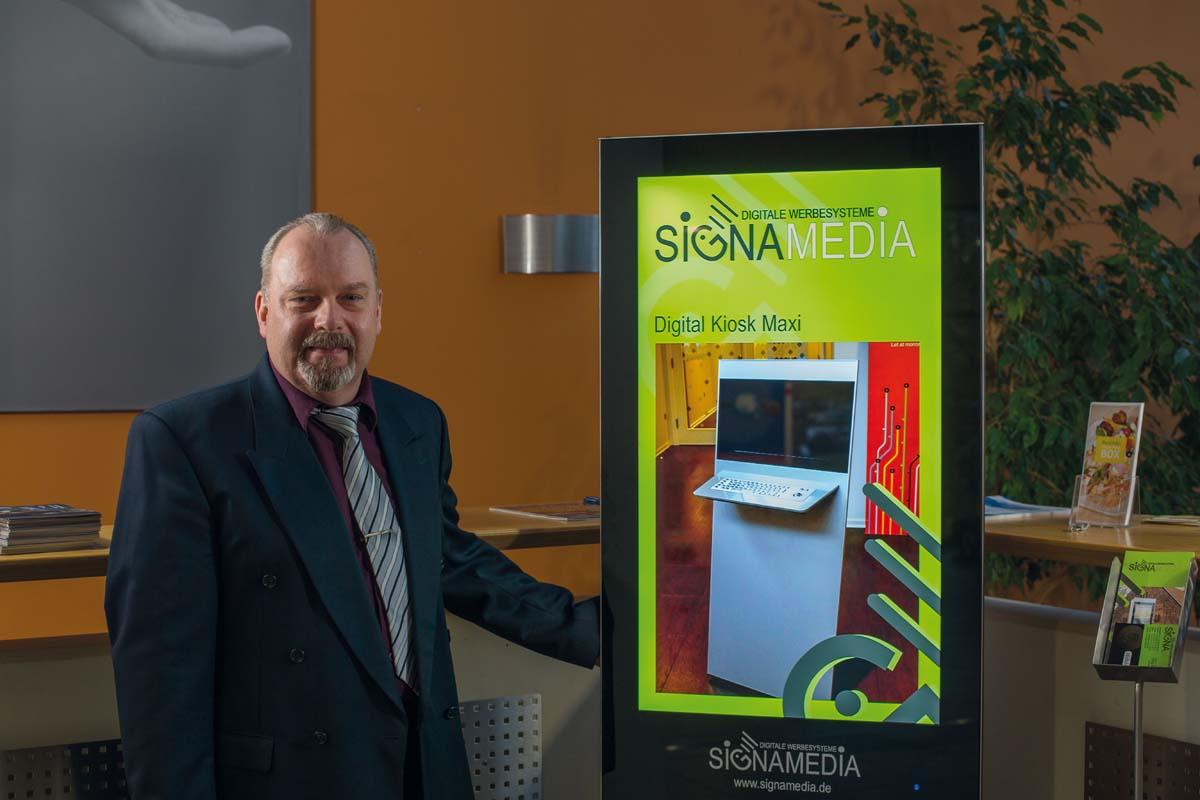 SIGNAMEDIA Geschäftsinhaber Jörg Muth mit Digital Signage Stele im Gründerzentrum TIG in Gießen